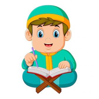 Gruby chłopiec z zielonym kaftanem czyta al koran