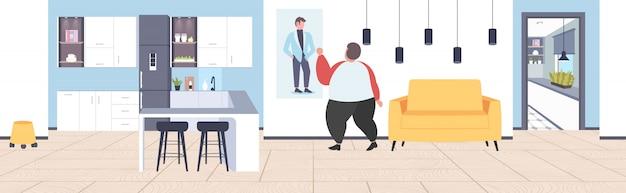 Gruby otyły mężczyzna patrząc na szczupłego faceta na zdjęciu utrata masy ciała motywacja koncepcja otyłości nowoczesne mieszkanie wnętrze domu