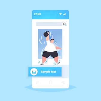 Gruby otyły mężczyzna podnoszenia nadwagą kettlebell facet robi ćwiczenia trening trening utrata masy ciała koncepcja smartphone ekran aplikacji mobilnej online