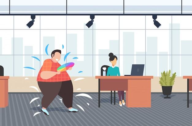 Gruby otyły mężczyzna projektant trzyma próbkę palety kolorów przewodnik nadwagą facet z katalogu kolorów koncepcja otyłości nowoczesne wnętrze biura