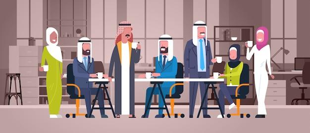 Grupa arabskich ludzi biznesu pić herbatę lub kawę siedzieć razem przy biurku w nowoczesnym biurze muzułmańskich pracowników zespołu w przerwie