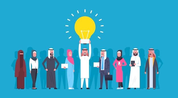 Grupa arabskich ludzi biznesu z liderem trzyma żarówkę nowa koncepcja pomysł arabski biznesmen i bizneswoman kreatywny zespół