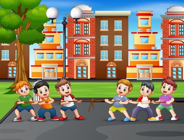Grupa chłopców grających w przeciąganie liny na korcie