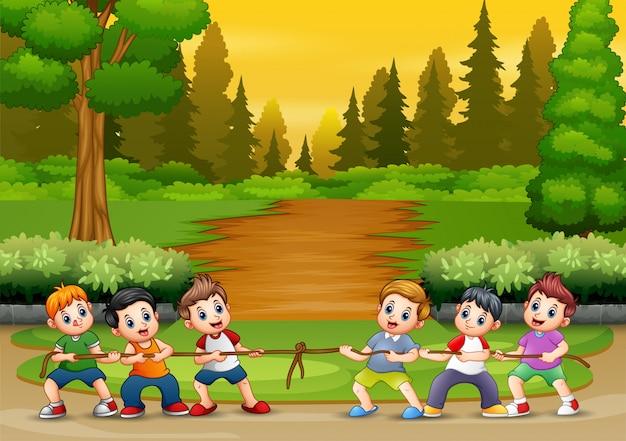 Grupa chłopców grających w przeciąganie liny w parku