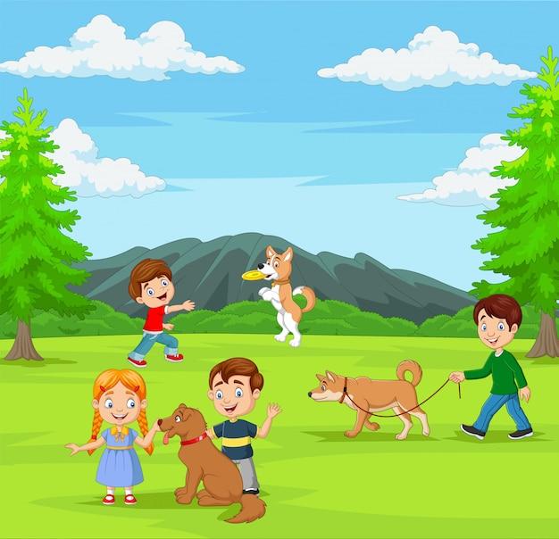 Grupa dzieci bawiące się z psami w parku
