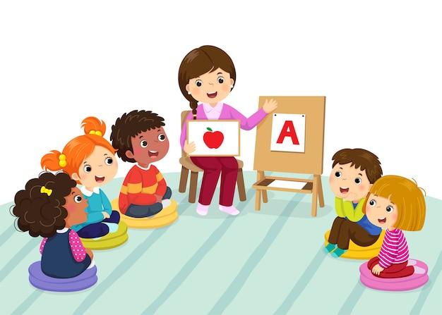 Grupa dzieci w wieku przedszkolnym i nauczyciel siedzi na podłodze. nauczyciel wyjaśniający alfabet dla dzieci
