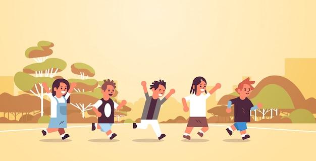Grupa dzieci w wieku szkolnym biegające razem grupa podstawowa wiek grupa uczniów zabawa na wolnym powietrzu mężczyzna kobieta uczniowie krajobraz tło płaskie pełnej długości poziomej
