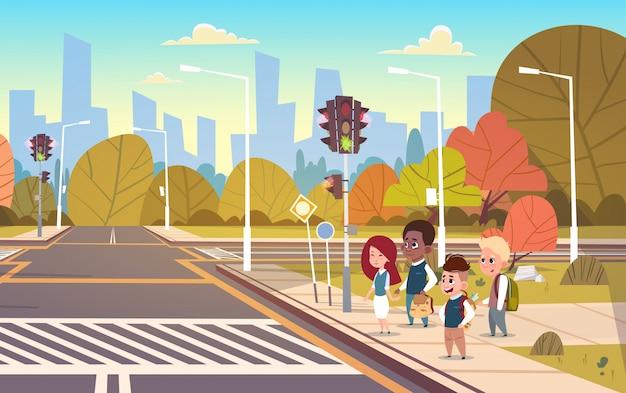 Grupa dzieci w wieku szkolnym czeka na zielone światło na skrzyżowaniu drogi na przejście dla pieszych
