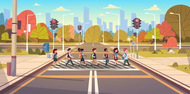 Grupa dzieci w wieku szkolnym przekraczania drogi na przejście dla pieszych