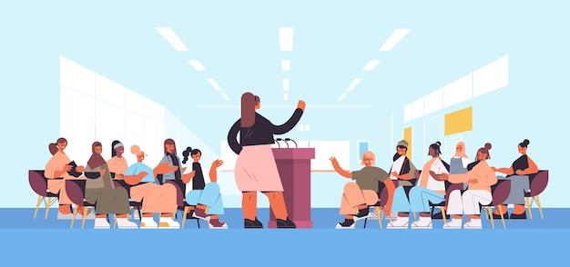 Grupa koleżanek rasy mieszanej dyskutująca podczas spotkania w klubie kobiet dziewczyny wspierające się nawzajem związek feministek koncepcja sala wykładowa wnętrze poziomej pełnej długości ilustracji wektorowych