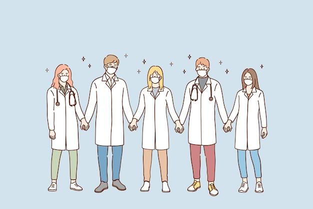 Grupa lekarzy w ochronne maski medyczne stojąc i trzymając się za ręce w zespole