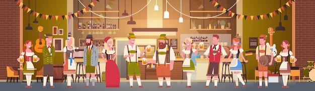 Grupa ludzi pije piwo w barze oktoberfest partyjnego świętowania mężczyzna i kobiety jest ubranym tradycyjnego odzieżowego fest pojęcie