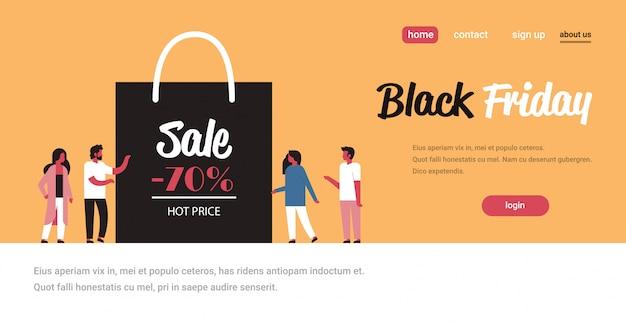 Grupa ludzi przy torbie na zakupy z dużym znakiem sprzedaży rabat promocyjny na święta w czarny piątek