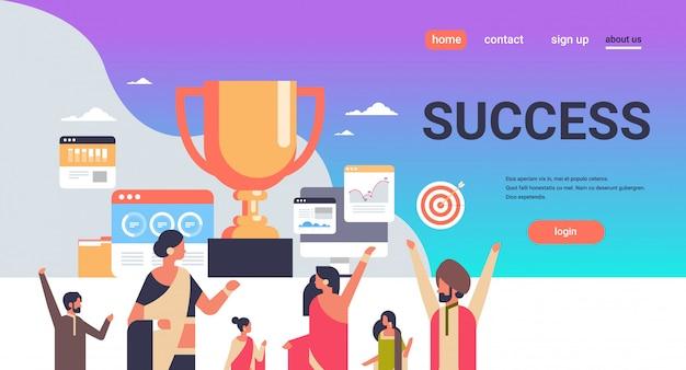 Grupa ludzi sukcesu w indiach trzyma puchar zdobywcy trofeum pierwsze miejsce koncepcja numer jeden strategia pracy zespołowej