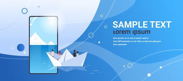 Grupa ludzi unoszących się na papierowej łodzi widok z tyłu mężczyźni kobiety zespół podróżujący na odkrycie owiec koncepcja smartfona ekran aplikacji mobilnej online