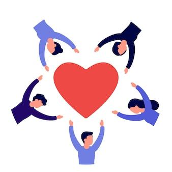 Grupa ludzi wraz z rękami w górze stoją w kręgu otaczają czerwone serce symbol miłości pomocy