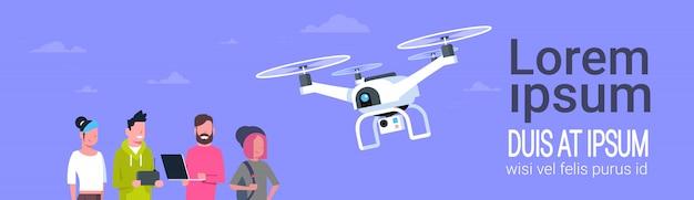 Grupa ludzi z gadżetami używając nowoczesnego drona
