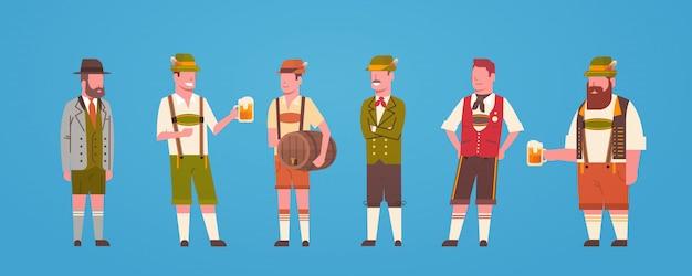 Grupa mężczyzna kelnerzy jest ubranym niemieckiego tradycyjnego odzieżowego męskiego trzyma kufel piwa oktoberfest pojęcie