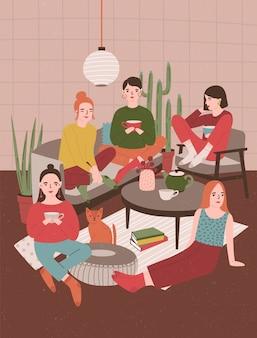 Grupa młodych kobiet siedzi w pokoju urządzonym w stylu skandynawskim, pije herbatę i rozmawia ze sobą