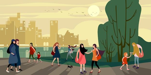 Grupa młodych ludzi miejskich chodzić wieczorem nabrzeża miasta latem