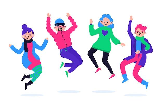 Grupa młodych ludzi ubranych w zimowe ubrania skoki