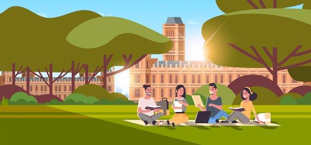 Grupa młodych nastoletnich studentów siedzi na trawie w kampusie stoczni edukacji koncepcja kolegium relaksujący i rozmawiający przed budynkiem uniwersytetu na zewnątrz poziomej pełnej długości