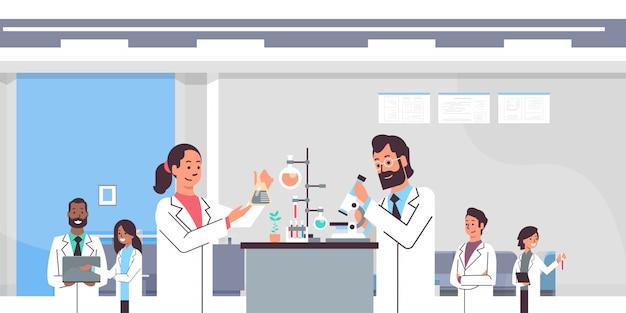 Grupa naukowców pracujących z mikroskopem w laboratorium robi badania kobieta mężczyzna eksperymenty naukowe mieszają lekarzy rasy w laboratorium portret wnętrze pracy