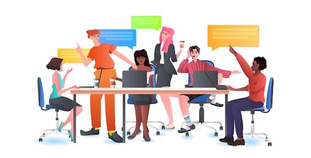 Grupa przedsiębiorców rasy mieszanej omawiająca podczas spotkania przy okrągłym stole bańka czatu pracy zespołowej