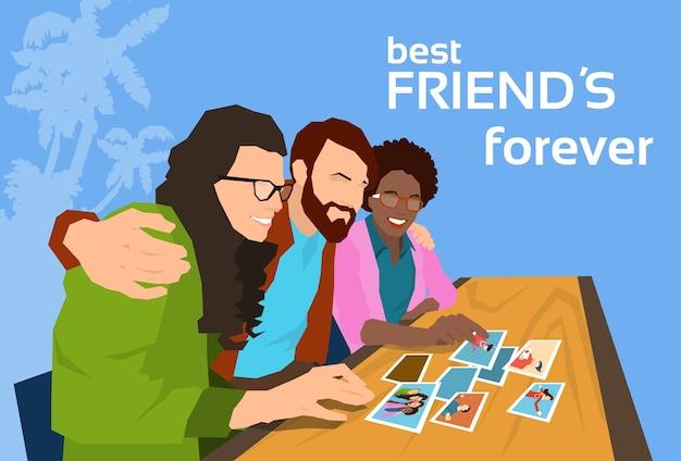 Grupa przyjaciół patrząc na zdjęcia szczęśliwy transparent dzień przyjaźni
