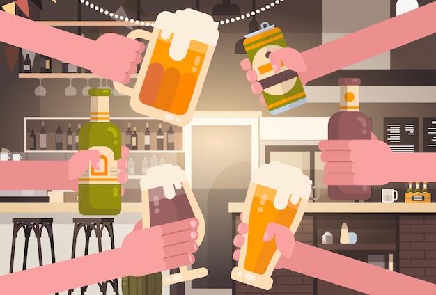 Grupa ręki clinking piwnych ludzi w pubie lub baru restauraci dopingu przyjęcia świętowania festiwalu pojęciu