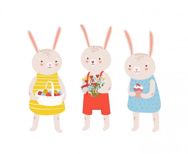 Grupa zabawnych uroczych króliczków lub królików trzymających tradycyjne prezenty wielkanocne - kosz z dekorowanymi jajkami, bukiet kwiatów, kulich. ilustracja kreskówka płaski na święto religijne.
