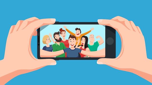 Grupowe selfie na smartfonie. zdjęcie portret przyjaznej drużyny młodzieżowej, przyjaciele robią zdjęcia na kreskówce z aparatu w telefonie
