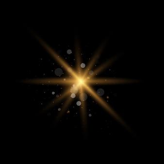 Gwiazda wybuchła iskierkami. zestaw żółtego świecącego światła wybucha na czarnym tle musujące magiczne cząsteczki pyłu. złoty brokat bright star. przezroczyste świecące słońce, jasny błysk