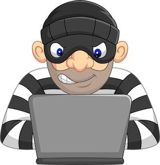 Hacker thief w masce kradnącej dane osobowe z komputera