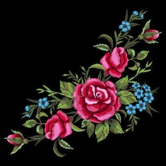 Haftowane czerwone róże i niebieskie kwiaty.