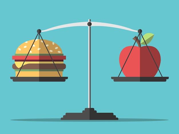 Hamburger i jabłko na wadze równowaga między szybkim i zdrowym jedzeniem odżywianie dietetyczne fitness