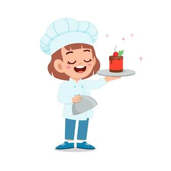 Happy cute little kid girl nosić mundur szefa kuchni i gotować tort urodzinowy