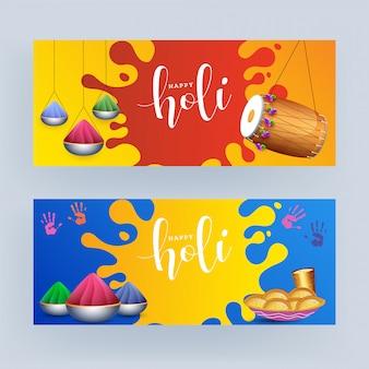 Happy holi text z dholak, kolorowymi miskami, szkłem thandai i indyjską słodyczą w dwóch kolorach.