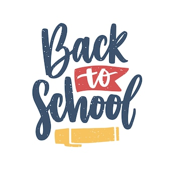 Hasło powrót do szkoły odręcznie czcionką kaligraficzną i ozdobione wstążką i pisakiem