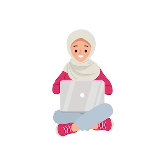 Hidżab kobieta siedzi i używa laptopa.