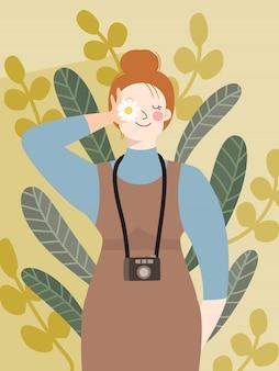 Hipster dziewczyna stoi przy ścianie i trzyma w oczach mały kwiatek.