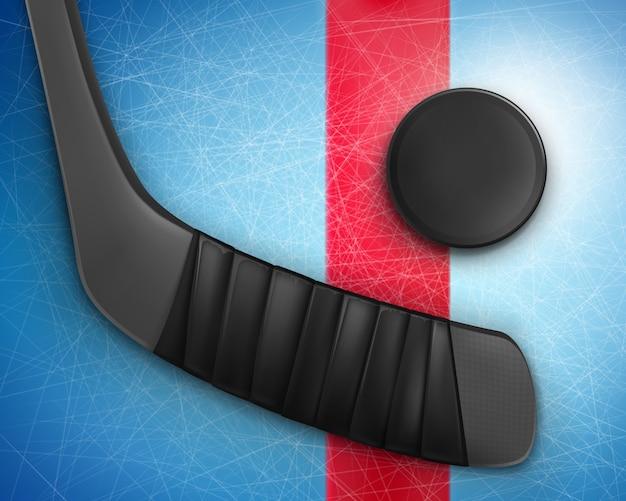 Hokejowy czarny kij i krążek na lodzie
