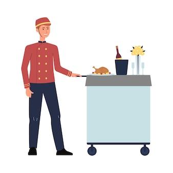 Hotelowy pracownik gastronomii w czerwonym mundurze pchający wózek z luksusowym posiłkiem.
