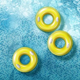 Ilustracja gumowych kółek do pływania z uchwytami unoszącymi się na niebieskim basenie, widok z góry
