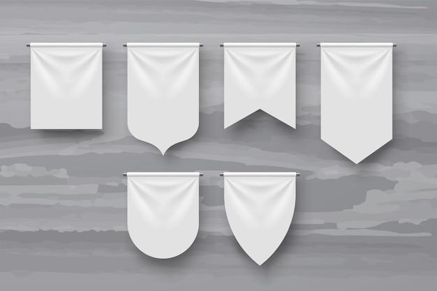 Ilustracja przedstawiająca różne kształty białe proporczyki z realistycznymi cieniami na szarym marmurze