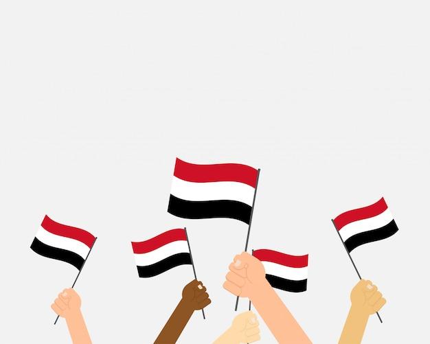 Ilustracja ręce trzymając flagi jemenu