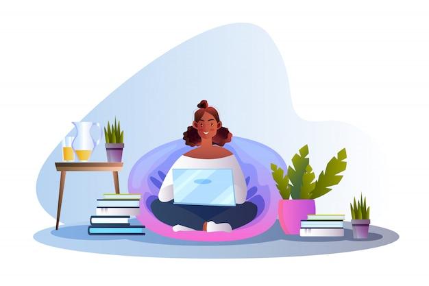 Ilustracja w stylu płaskiej z uśmiechnięta młoda dziewczyna siedzi na poduszce za pomocą laptopa.
