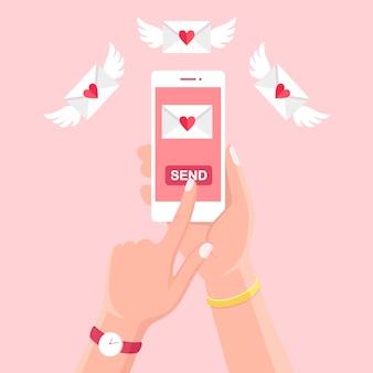 Ilustracja walentynki. wysyłaj lub odbieraj miłosne sms, list, e-mail z białego telefonu komórkowego. ludzką ręką trzymać telefon komórkowy, smartfon na tle. koperta z czerwonym sercem.