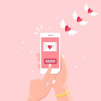 Ilustracja walentynki. wysyłaj lub otrzymuj miłosne smsy, listy, e-maile z telefonu komórkowego. biały telefon w ręku na białym tle na tle. latająca koperta z czerwonym sercem, skrzydłami. płaska konstrukcja