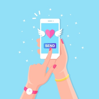 Ilustracja walentynki. wysyłaj lub otrzymuj miłosne smsy, listy, e-maile z telefonu komórkowego. biały telefon w ręku na tle. latające czerwone serce ze skrzydłami.